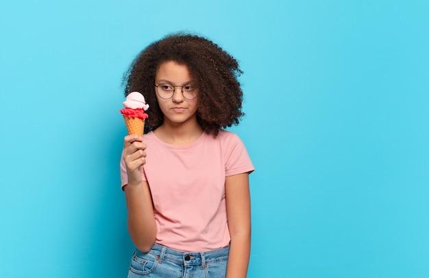 Симпатичный афро-подросток грустит, расстроен или зол, смотрит в сторону с негативным отношением и хмурится в знак несогласия. концепция шумерского мороженого
