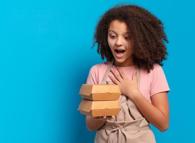 Довольно афро-шеф-повар девушка-подросток с коробками для гамбургеров на вынос