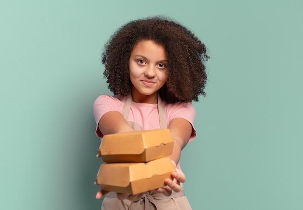 テイクアウトのハンバーガーボックスを持つかなりアフロティーンエイジャーの女の子のシェフ