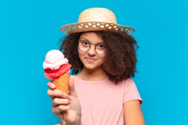 帽子とアイスクリームを持っているかなりアフロティーンエイジャーの女の子。夏のコンセプト