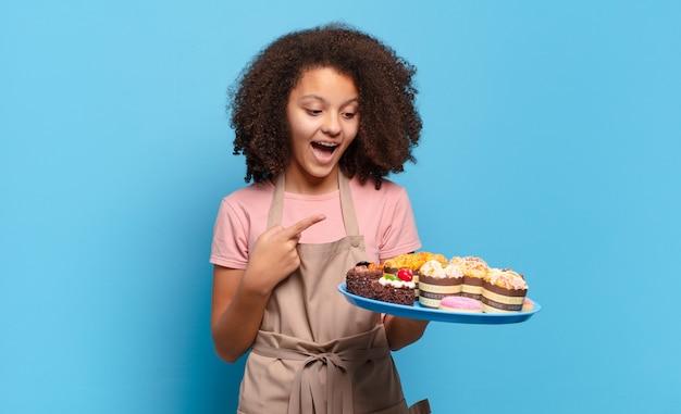 Довольно афро-подросток выглядит взволнованным и удивленным, указывая в сторону и вверх, чтобы скопировать пространство. юмористическая концепция пекаря