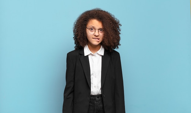 Pretty afro teenager looking puzzled and confused, biting lip with a nervous gesture, not knowing the answer to the problem. humorous business concept