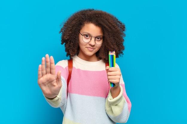 真面目で、厳しく、不機嫌で、怒っているように見えるかなりアフロのティーンエイジャーは、開いた手のひらが停止ジェスチャーをしていることを示しています。学生の概念