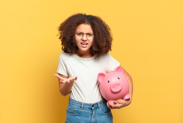 Pretty afro teenager looking shocked, with hand and peeking between fingers. savings concept