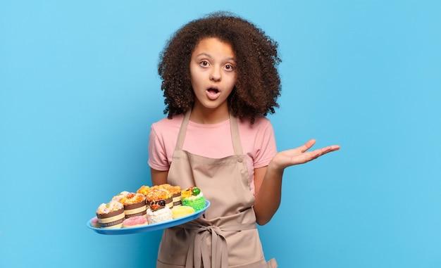 Симпатичный афро-подросток выглядит удивленным и шокированным, с отвисшей челюстью держит объект открытой рукой сбоку. юмористическая концепция пекаря