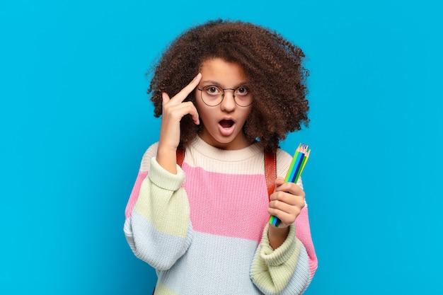 Довольно афро-подросток выглядит удивленным, с открытым ртом, шокированным, осознающим новую мысль, идею или концепцию. студенческая концепция