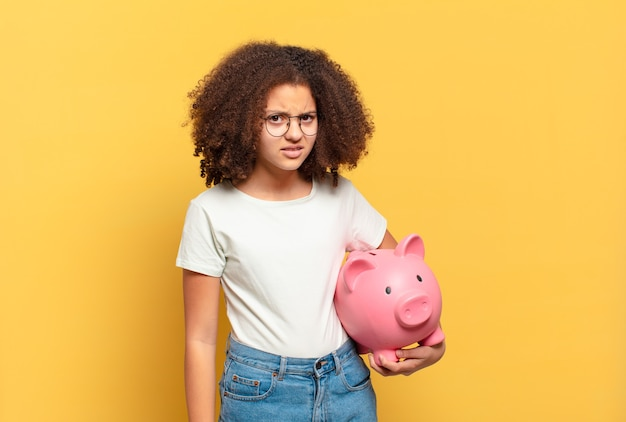 Pretty afro teenager looking unhappy and stressed, suicide gesture making gun sign with hand, pointing to head. savings concept