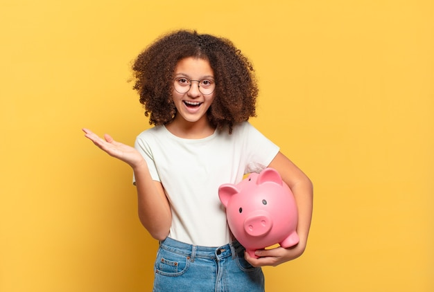 Pretty afro teenager making capice or money gesture, telling you to pay your debts!
