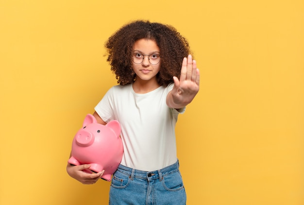 Pretty afro teenager making stop gesture. savings concept
