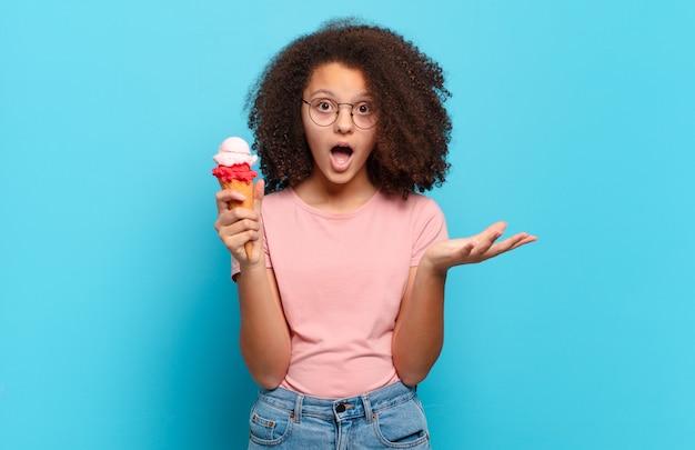 Симпатичный афро-подросток с открытым ртом изумлен, потрясен и изумлен невероятным сюрпризом. концепция шумерского мороженого