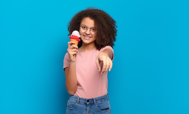 Pretty afro teenager pointing at camera with a satisfied, confident, friendly smile, choosing you. sumer ice cream concept