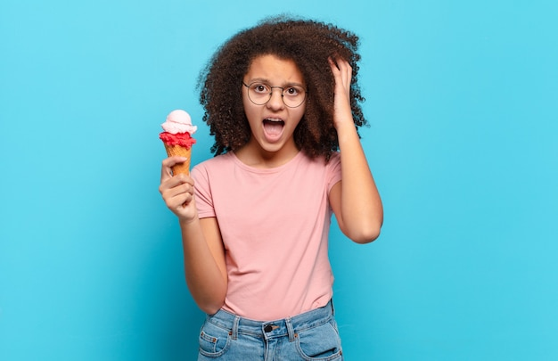 Pretty afro teenager screaming with hands up in the air, feeling furious, frustrated, stressed and upset. sumer ice cream concept