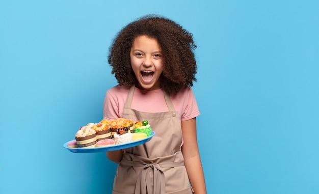 Симпатичный афро-подросток агрессивно кричит, выглядит очень злым, расстроенным, возмущенным или раздраженным, кричит «нет». юмористическая концепция пекаря