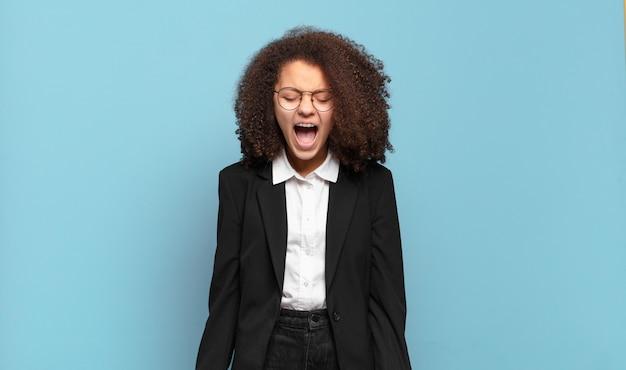 Симпатичный афро-подросток агрессивно кричит, выглядит очень злым, расстроенным, возмущенным или раздраженным, кричит «нет». юмористическая бизнес-концепция