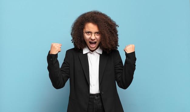 Довольно афро-подросток агрессивно кричит с сердитым выражением лица или со сжатыми кулаками, празднуя успех. юмористическая бизнес-концепция