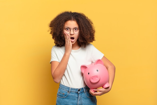 Pretty afro teenager shrugging, feeling confused and uncertain, doubting with arms crossed and puzzled look. savings concept