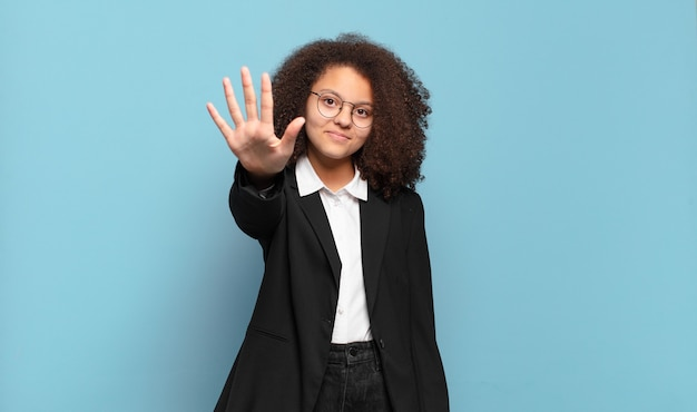 Симпатичный афро-подросток улыбается и выглядит дружелюбно, показывает пятый или пятый номер рукой вперед и ведет обратный отсчет
