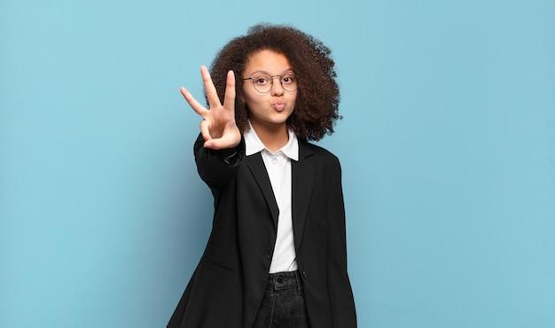 Симпатичный афро-подросток улыбается и выглядит дружелюбно, показывает номер три или треть рукой вперед, отсчитывая. юмористическая бизнес-концепция