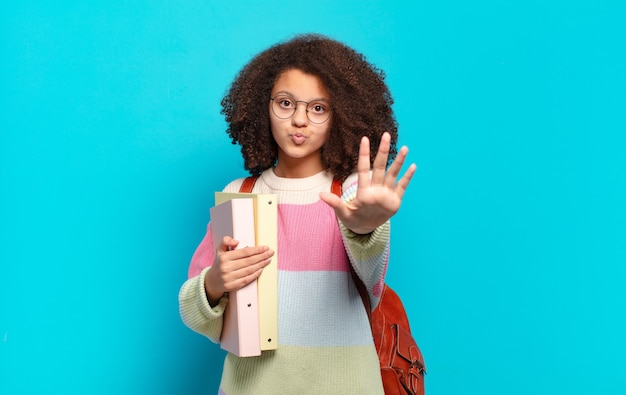 Pretty afro teenager smiling and looking friendly, showing number five or fifth with hand forward, counting down. student concept