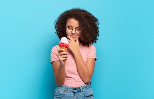 Довольно афро-подросток улыбается со счастливым, уверенным выражением лица, положив руку на подбородок, недоумевая и глядя в сторону. концепция шумерского мороженого