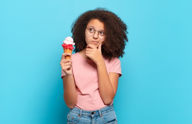 Pretty afro teenager thinking, feeling doubtful and confused, with different options, wondering which decision to make. sumer ice cream concept