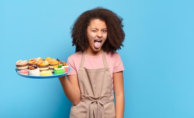 쾌활하고 평온하고 반항적 인 태도, 농담 및 혀를 내밀고있는 예쁜 아프리카 십대