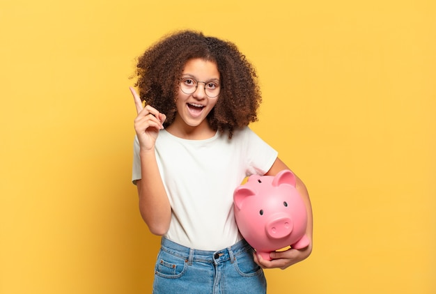 Pretty afro teenager with mouth and eyes wide open and hand on chin, feeling unpleasantly shocked, saying what or wow. savings concept