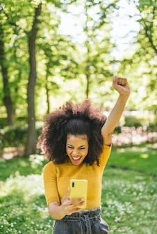 Симпатичная афро-женщина болтает по мобильному телефону, празднуя хорошие новости с поднятым кулаком. в парке. выборочный фокус.