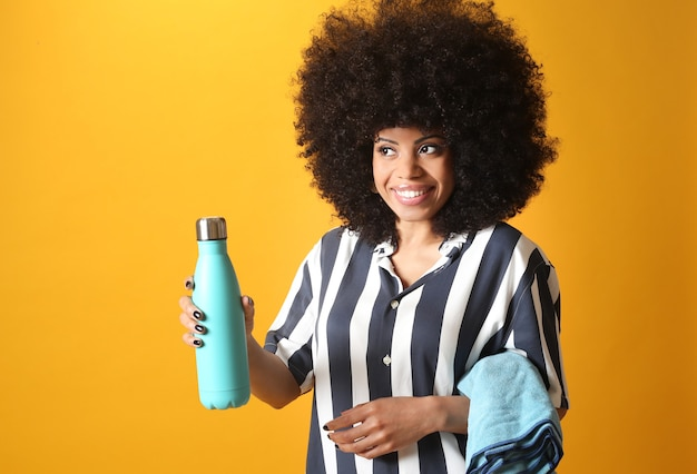 かなりアフロの女性は、黄色の背景にタオルと飲み物、アスリートを保持します