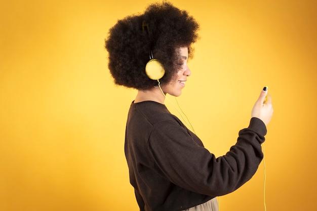 ヘッドフォンとスマートフォン、黄色の背景で音楽を聴いているかなりアフロの女性