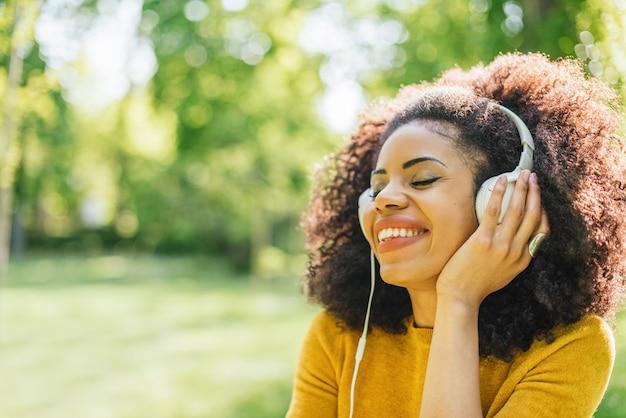 かなりアフロの女性が庭で踊るヘッドフォンで音楽を聴きます。セレクティブフォーカス。