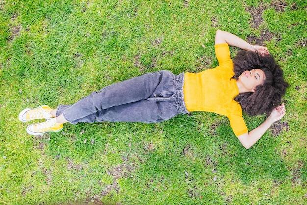 庭で仰向けに横たわっているかなりアフロの女性。航空写真。セレクティブフォーカス。
