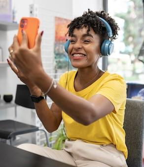 彼女のスマートフォンでビデオ通話で話しているかなりアフロの女性