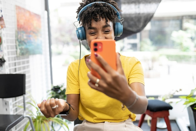 Pretty afro woman talking on video call with her smartphone
