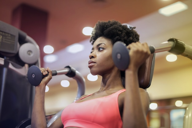 Pretty afro woman working out in the gym