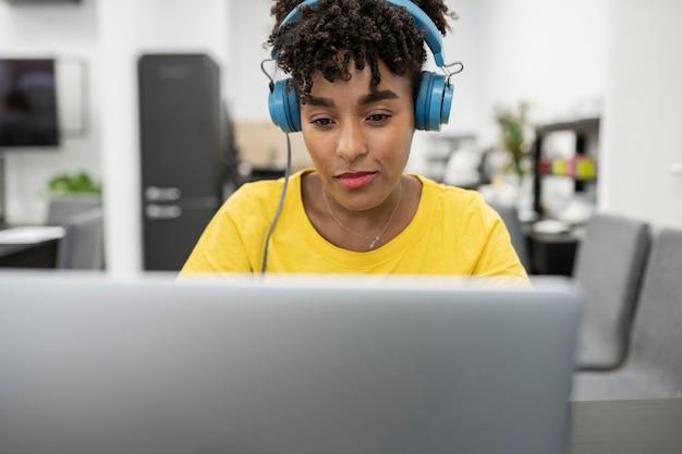 クライアントに答えるヘッドフォンで働くかなりアフロの女性