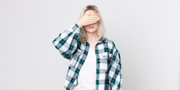 片手で目を覆っているかなりアルビノの女性は、恐怖や不安を感じ、不思議に思ったり、盲目的に驚きを待っています