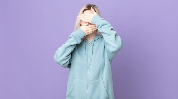 カメラにノーと言って両手で顔を覆っているかわいいアルビノの女性!写真を拒否したり、写真を禁止したりする