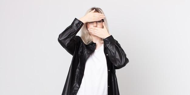 두 손으로 얼굴을 가린 예쁜 알비노 여성이 카메라를 거부합니다! 사진을 거부하거나 사진을 금지