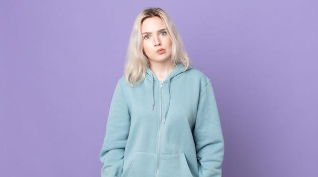 Симпатичная женщина-альбинос смущена и сомневается, задается вопросом или пытается выбрать или принять решение