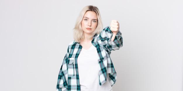 Красивая женщина-альбинос чувствует себя сердитой, сердитой, раздраженной, разочарованной или недовольной, показывая большой палец вниз с серьезным взглядом