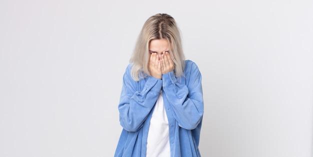 예쁜 알비노 여성은 슬프고, 좌절하고, 긴장하고, 우울하고, 두 손으로 얼굴을 가리고, 울고 있다