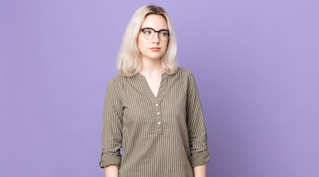 Симпатичная женщина-альбинос грустит, расстроена или злится и смотрит в сторону с негативным отношением, хмурясь в знак несогласия.