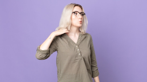 かなりアルビノの女性は、ストレス、不安、疲れ、欲求不満を感じ、シャツの首を引っ張って、問題で欲求不満に見えます