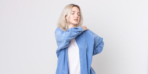 Симпатичная женщина-альбинос чувствует усталость, стресс, тревогу, разочарование и депрессию, страдает от боли в спине или шее