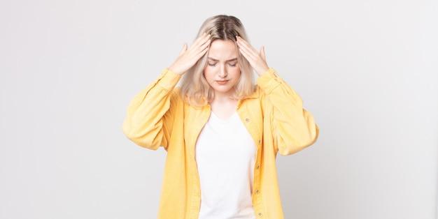 Симпатичная женщина-альбинос выглядит напряженной и расстроенной, работает под давлением с головной болью и обеспокоена проблемами