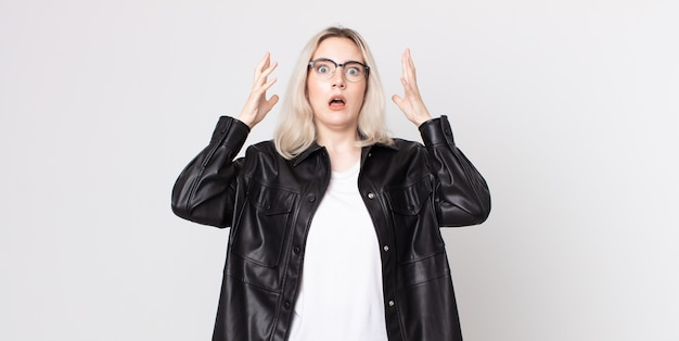 Pretty albino woman screaming with hands up in the air, feeling furious, frustrated, stressed and upset
