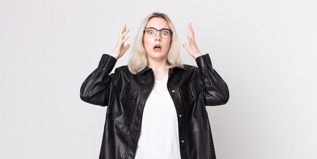 Симпатичная женщина-альбинос кричит с поднятыми руками, чувствуя ярость, разочарование, стресс и расстройство