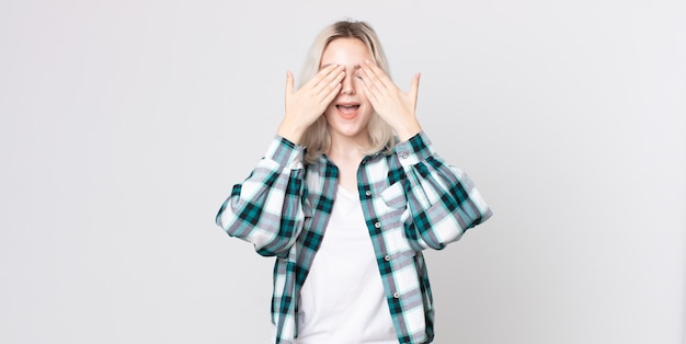 Симпатичная женщина-альбинос улыбается и чувствует себя счастливой, прикрывая глаза обеими руками и ожидая невероятного сюрприза