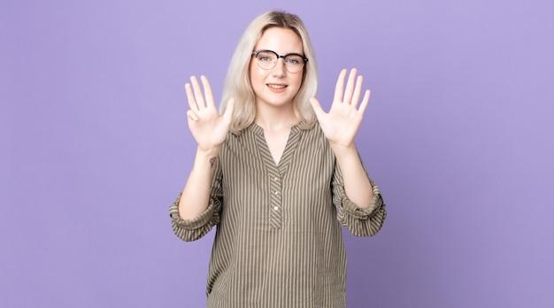 笑顔でフレンドリーに見えるかなりアルビノの女性、前に手を前に9番または9番を示し、カウントダウン